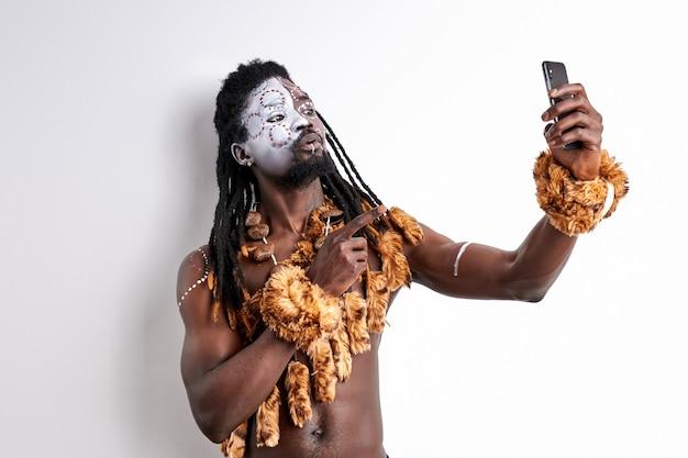 L'uomo di colore guarda il telefono cellulare parlando, prendendo foto isolato sopra il muro bianco