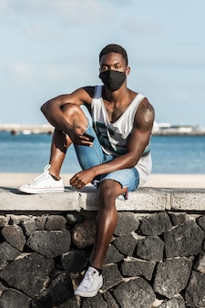 Uomo di colore in maschera e con smartphone in riva al mare