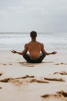 Uomo di colore che medita in spiaggia