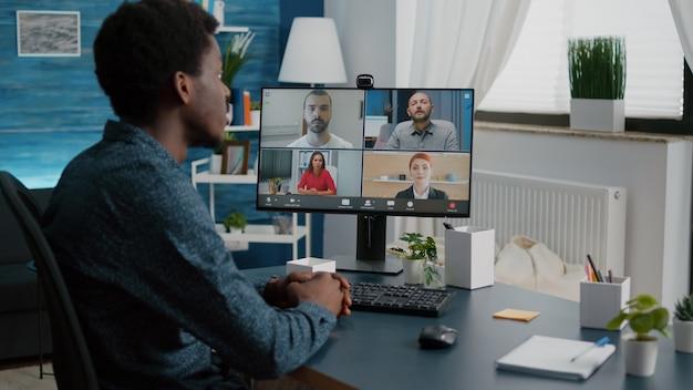 Uomo di colore in chat conferenza internet online con i suoi colleghi, lavoro remoto da casa, utilizzando la comunicazione web in teleconferenza con la webcam. la tecnologia a distanza parla