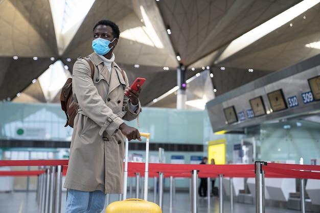 Uomo di colore in piedi all'aeroporto che indossa una maschera protettiva per il viso durante l'epidemia di virus, covid-19