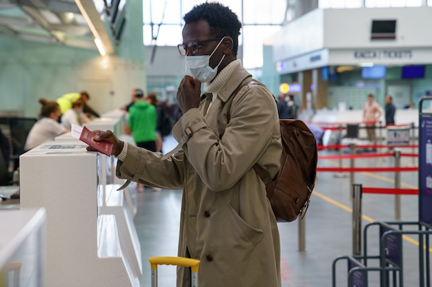 Un uomo di colore è in piedi ai banchi del check-in in aeroporto, consegna il passaporto a un agente, indossa una maschera.