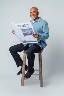 Uomo di colore su uno sgabello che legge un giornale