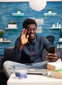 Uomo di colore che parla in videoconferenza online