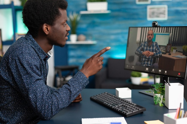 Uomo di colore che parla con l'insegnante di handicap disabile remoto durante la conferenza di videochiamata online che lavora alla presentazione di marketing. adolescente che fa una teleconferenza di telelavoro utilizzando il computer
