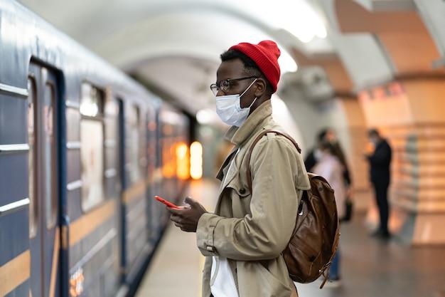 L'uomo di colore indossa una maschera facciale come protezione contro il virus covid-19, in piedi nella metropolitana, usando il cellulare.