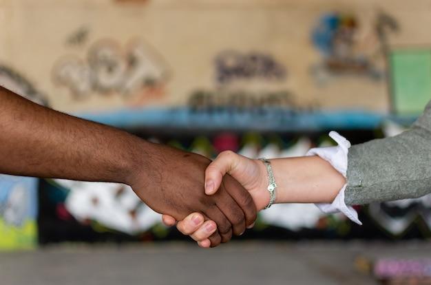Uomo nero e donna bianca che tengono le mani. concetto di unione. stop al razzismo.