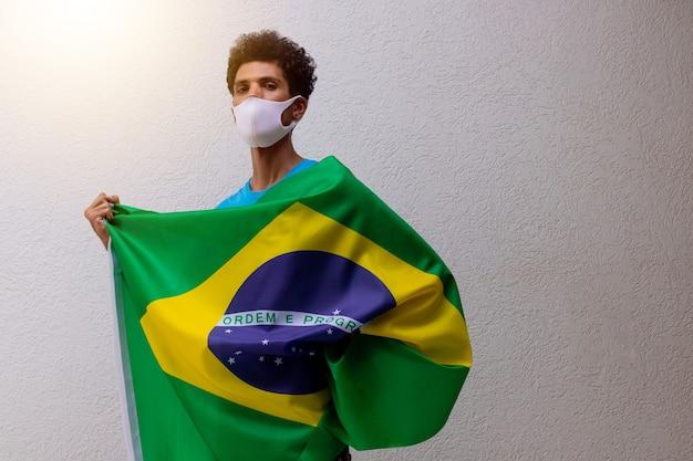 Uomo di colore con la maschera pandemica che tiene una bandiera del brasile isolata su bianco. bandiera e immagine del concetto di festa dell'indipendenza.