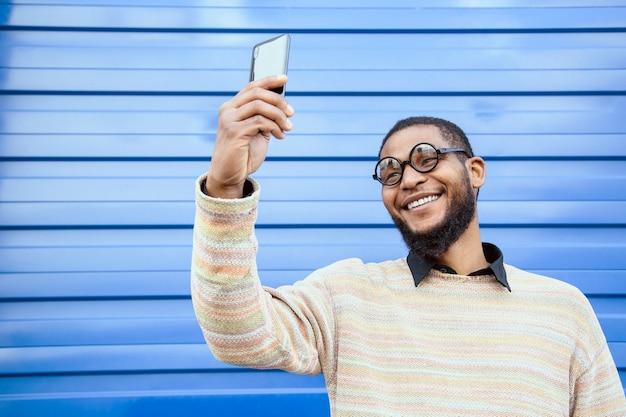 Uomo di colore con occhiali rotondi da nerd, sorridente, che si fa un selfie con il tuo cellulare.