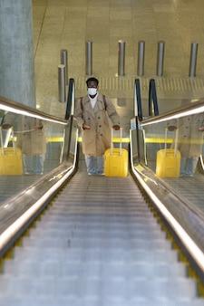 L'uomo nero con la valigia si trova sulla scala mobile in aeroporto indossa la maschera per il viso durante la pandemia covid-19.