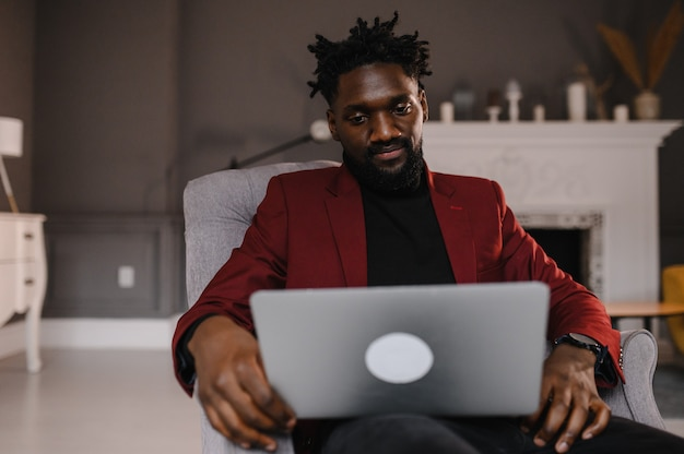 Uomo nero che lavora da casa avendo videoconferenza di gruppo online sul portatile