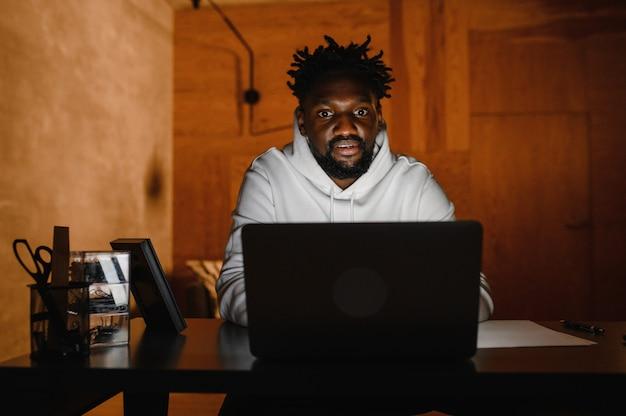 Un uomo di colore lavora a un laptop primo piano delle sue videoconferenze sul viso