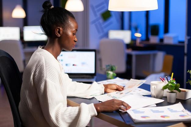 Gestore nero che analizza grafici e statistiche finanziarie dai documenti che fanno gli straordinari