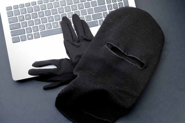 Maschera nera e guanti neri su un computer portatile