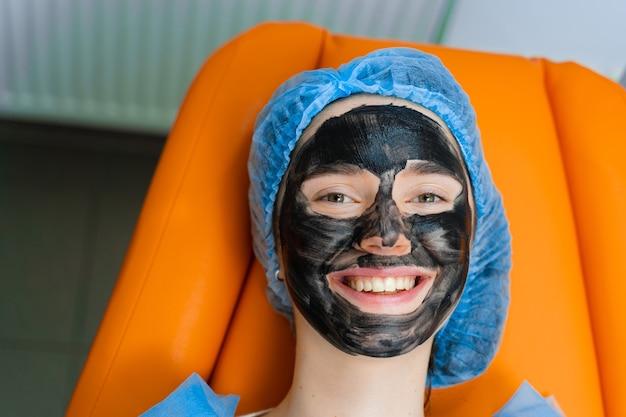 Maschera nera sul viso della ragazza per il peeling al carbonio. dermatologia e cosmetologia. usando il laser chirurgico.