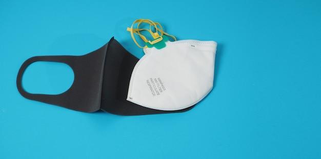La maschera nera e la maschera n 95 sono isolate su sfondo blu.