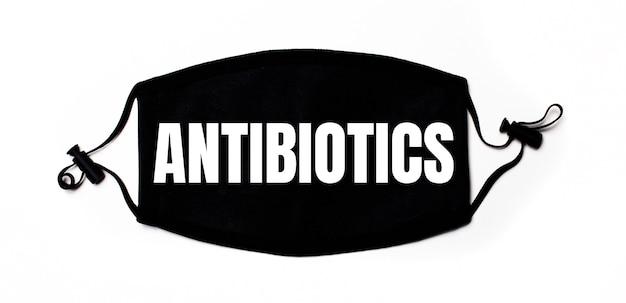 Maschera facciale medica nera su sfondo chiaro con la scritta antibiotics