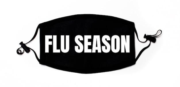 Maschera medica nera su sfondo chiaro con la scritta flu season