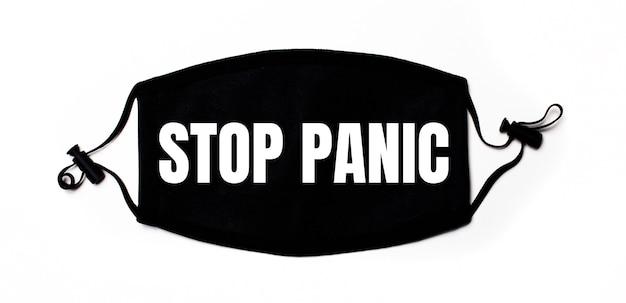 Maschera medica nera su una superficie chiara con la scritta stop panic