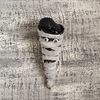 Gelato fondente nero in cono di cialda a forma di mummia per la festa di halloween