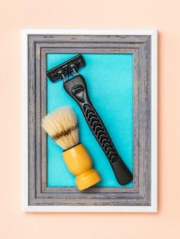 Rasoio da uomo nero e pennello da barba in una cornice su sfondo blu. collage. minimalismo. creatività creativa moderna.