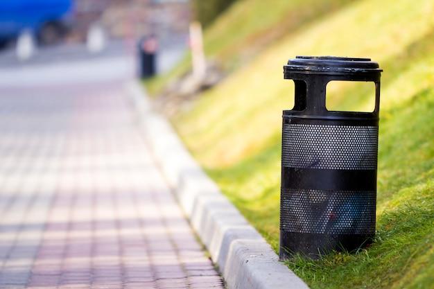 Bidone della spazzatura nero del metallo in parco
