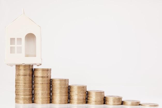 Un modello nero di un'auto e di una casa con monete sotto forma di istogramma