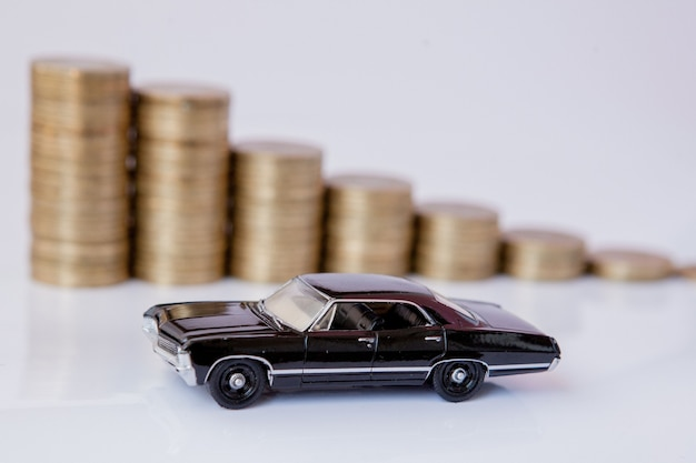 Un modello nero di un'auto con monete sotto forma di un istogramma su uno sfondo bianco