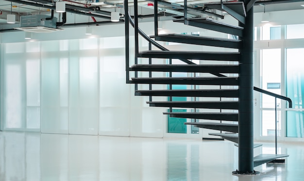 Scala a chiocciola moderna nera nell'ufficio di affari con le finestre, progettazione interna contemporanea delle scala del pavimento Foto Premium