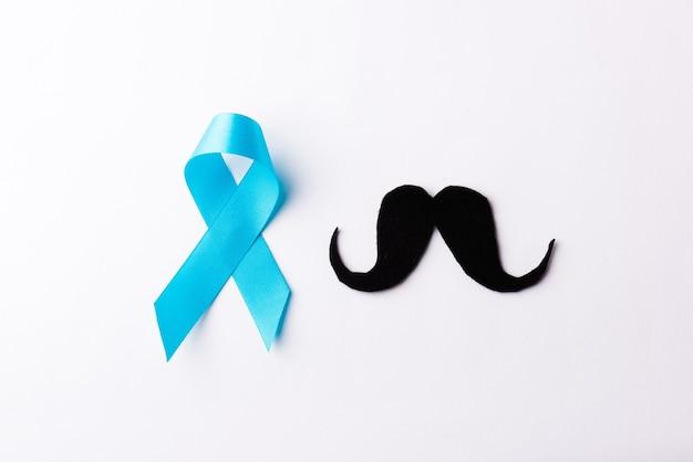 Carta baffi neri e nastro azzurro, concetto di baffi di novembre