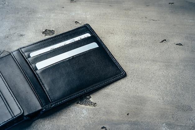 Nuovo portafoglio in pelle nera su sfondo grigio cemento
