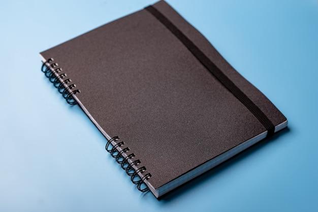Taccuino nero su sfondo blu. formazione, concetto di diario.