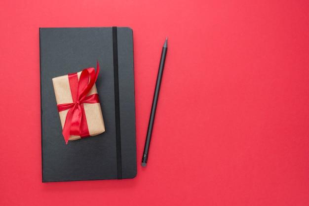 Taccuino nero su fondo rosso con un contenitore di regalo. concetto di san valentino.