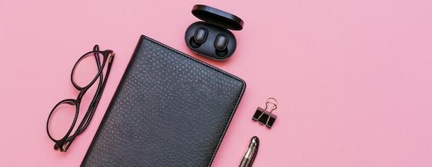 Taccuino nero con occhiali e cuffie wireless con penna su sfondo rosa torna al concetto di scuola...