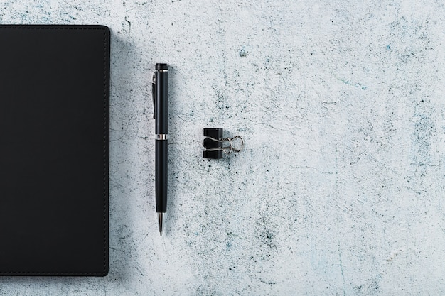 Blocco note nero con una penna nera su sfondo grigio. vista dall'alto, concetto minimalista. spazio libero.