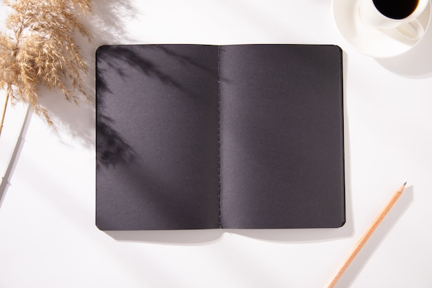 Blocco note nero con tazza di caffè ed erba sul tavolo