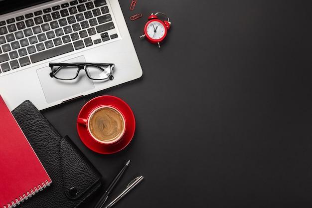 Tavolo da ufficio nero con computer portatile a schermo vuoto, sveglia, notebook, tazza di caffè e altro ufficio. vista dall'alto con spazio per la copia.