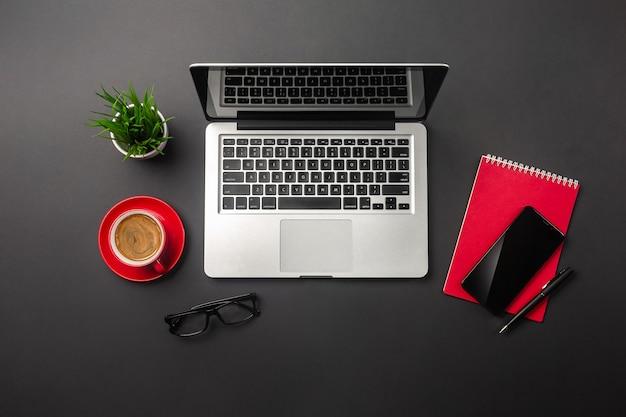 Tavolo da ufficio nero con computer portatile a schermo vuoto, notebook, telefono cellulare e tazza di caffè rossa. vista dall'alto.