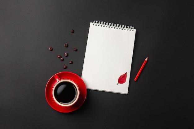 Desktop da ufficio nero con tazza rossa, chicchi di caffè e notebook. vista dall'alto con copia spazio