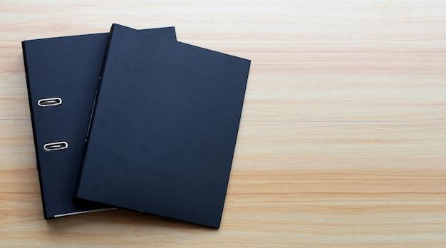 Cartelle nere dell'ufficio su fondo di legno di struttura.