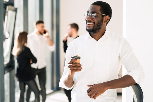 Impiegato nero che beve caffè in pausa