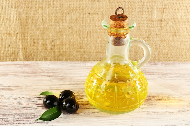 Olive nere con foglie verdi vicino all'olio può su tavola di legno verniciato, su sfondo di tela