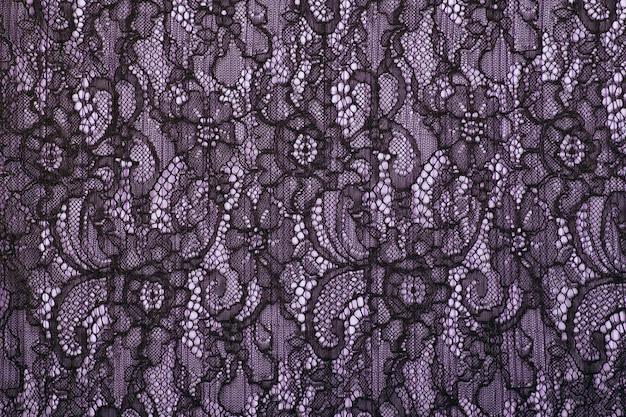 Trama di sfondo nero pizzo traforato. guipure nera. tessuto nero con ornamento. sfondo di pizzo nero con motivo a forma di fiore