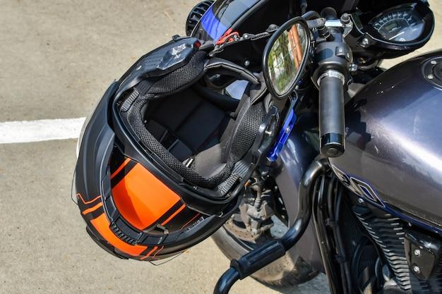 Il casco da motociclista nero-arancio è appeso al manubrio della moto. protezione durante la guida in moto