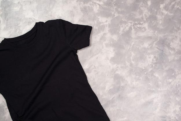 T-shirt in vernice nera con copia spazio. mockup di t-shirt, piatto lay. tavolo moderno in cemento.