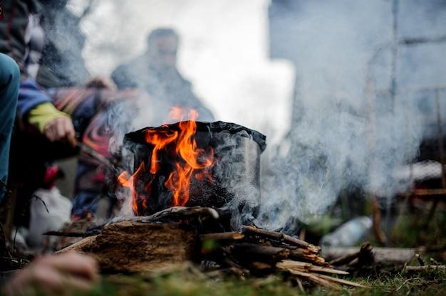 Padella nera con un piatto in piedi sul fuoco sopra il gruppo di amici