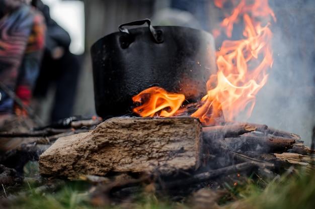 Padella nera con un piatto in piedi sul fuoco sopra il gruppo di persone