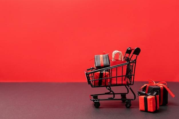 Sacchetti di carta neri e scatole regalo nel carrello su colore rosso