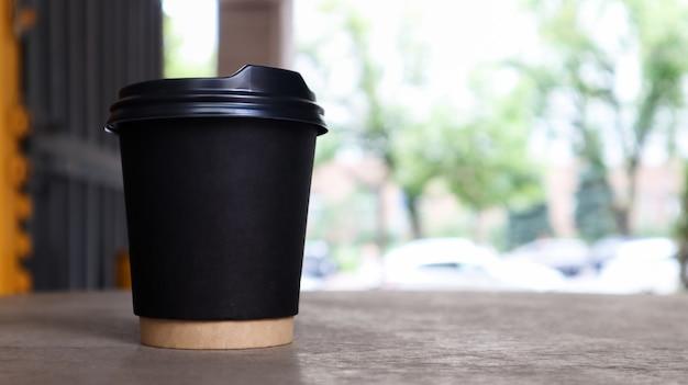 Tazza di carta nera senza testo e logo con caffè con coperchio in plastica su un tavolo di legno di una caffetteria di strada in città. copia spazio.