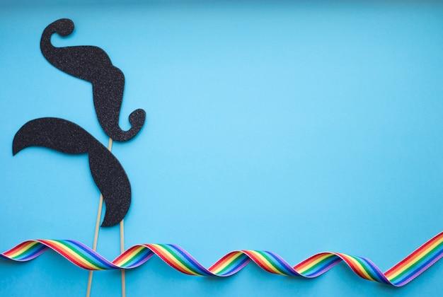 Baffi di carta nera su un bastone e nastro arcobaleno su sfondo blu. pride lgbt concept
